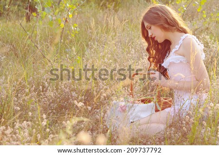 young woman gathering herbs in the field on the sunset - stock photo