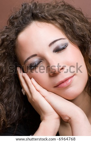 Young woman gentle lying her head in her hands.
