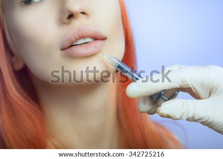 Young Woman Geting an Injection in her Lips in Beauty salon. Beauty Injections -Woman in the beautician office. Increase the Lips by Hyaluronic acid, Contouring procedure, revitalization