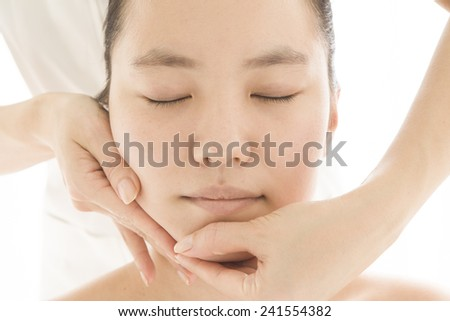 Young woman getting a face massage in spa salon