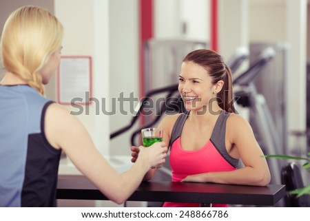 Young woman getting a high energy drink at the gym smiling as the girl behind the bar hands over the glass of refreshment after a workout - stock photo
