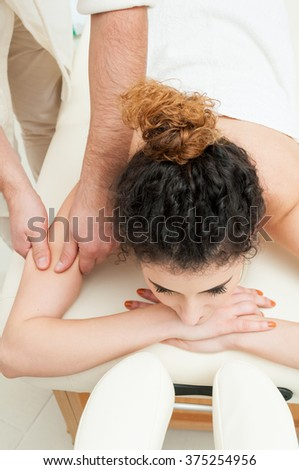 Young woman getting a spa massage of shoulder and pamper in spa center - stock photo