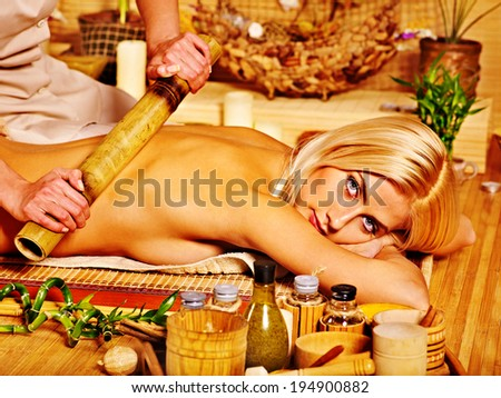 Young woman getting bamboo massage. Male therapist. - stock photo