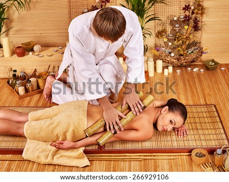 Young woman getting bamboo massage. Male therapist. Two people. - stock photo