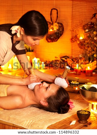 Young woman getting facial herbal massage ball. - stock photo