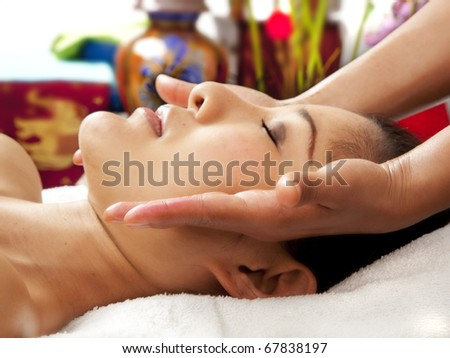 young woman getting facial massage - stock photo