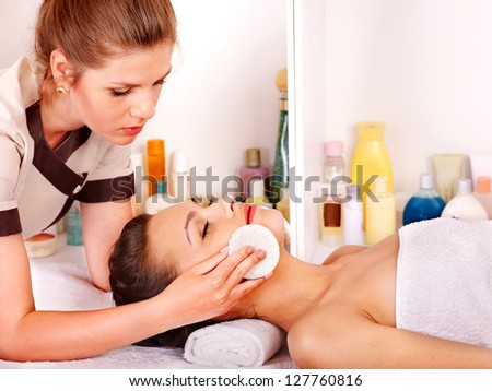 Young woman getting facial  massage in beauty spa.