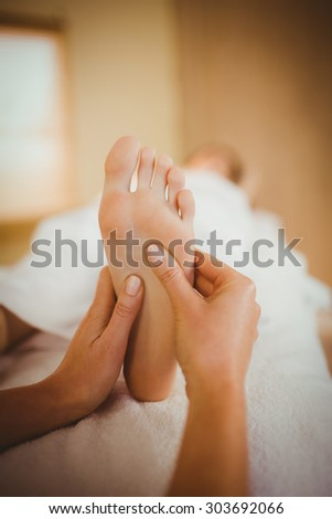 Young woman getting foot massage in therapy room