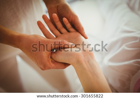 Young woman getting hand massage in therapy room - stock photo