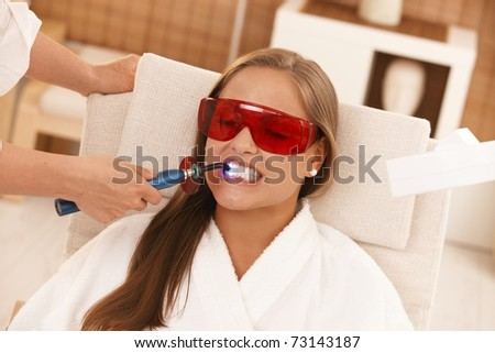 Young woman getting laser tooth whitening treatment at spa.?