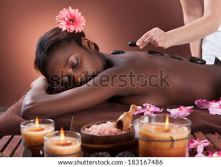 Young woman getting lastone therapy at spa salon - stock photo