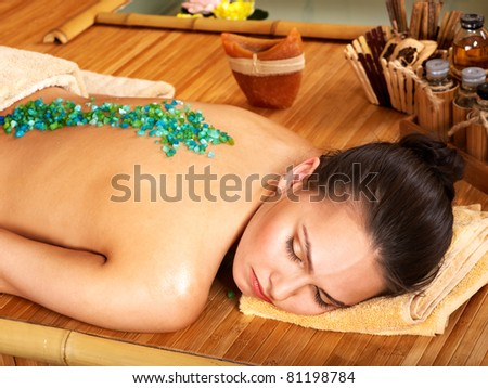 Young woman getting salt massage. - stock photo