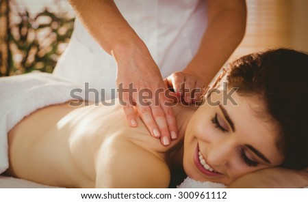 Young woman getting shoulder massage in therapy room - stock photo