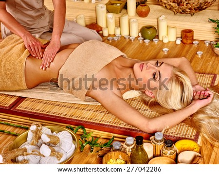 Young woman getting stomach massage in bamboo spa. Hand up. - stock photo