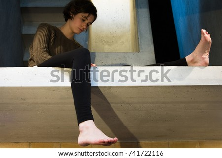 young woman, girl sitting on the concrete floor