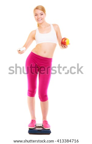 Young woman girl standing on weighing scale holding pills and apple. Choice between synthetic vitamins natural. Health care. Healthy lifestyle nutrition concept. Isolated on white background.  - stock photo