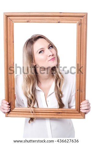 Young woman giving a playful posture holding a photo frame - stock photo
