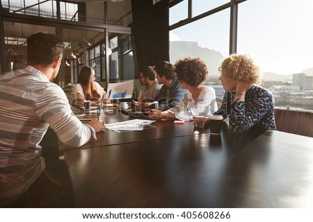 Young woman giving a presentation to colleagues in office. Mixed race team of creative professionals in a meeting at office. - stock photo