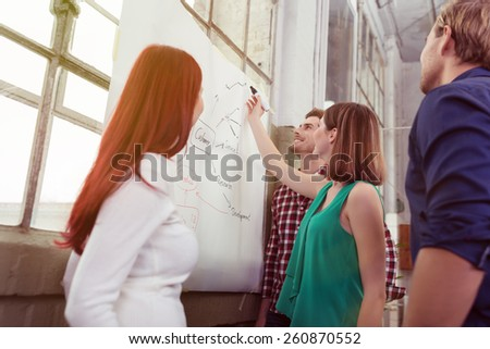 Young woman giving a presentation to her business colleagues or team standing drawing a flow chart on a flip chart in the office - stock photo