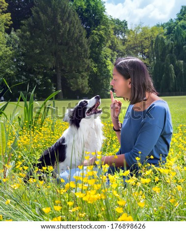 Young woman giving her border collie dog a reprimand in the park - stock photo