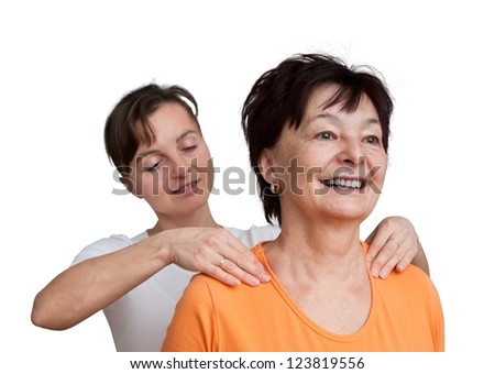 Young woman giving massage to senior - isolated on white - stock photo