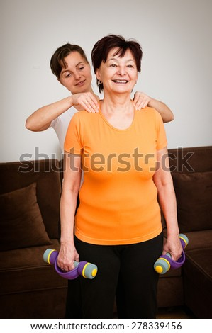 Young woman giving neck massage to her mother which is relaxing after exercise with barbells at home - stock photo