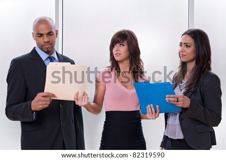 Young woman giving tasks to her colleagues who look skeptical. - stock photo