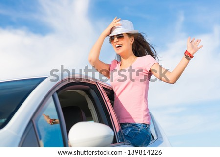 young woman got out of the car window, holds the hand hat, waving his hand and laughing