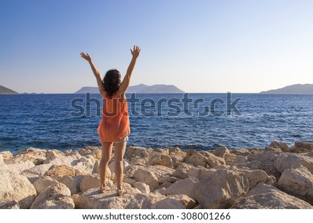 Young woman greets the sun on the beach