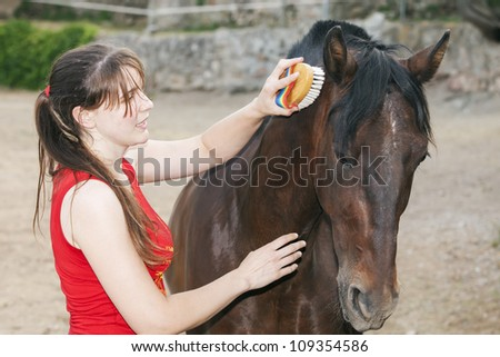 young woman grooming her horse - stock photo