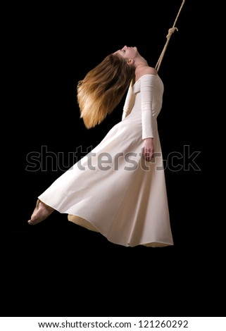Young woman gymnast in white dress on rope on black background - stock photo