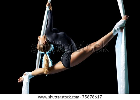 Young woman gymnast. On black background. - stock photo