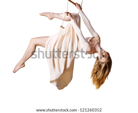 Young woman gymnast  on rope-ladder on white background - stock photo