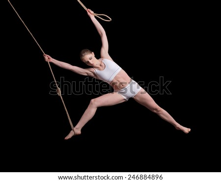 Young woman gymnast on rope on black background  - stock photo