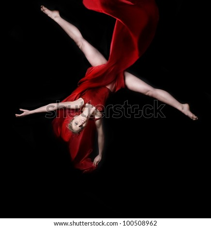Young woman gymnast wearing red dress on rope on black background - stock photo