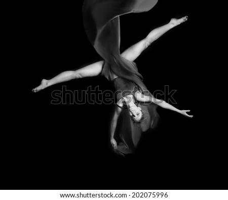 Young woman gymnaston rope on black background   - stock photo