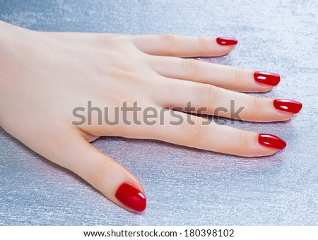 Young woman hand on silver surface. - stock photo
