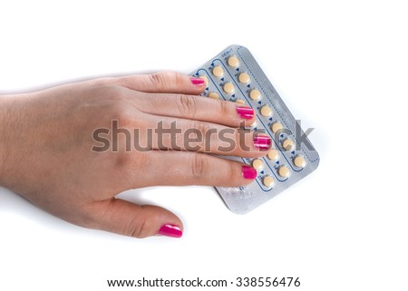young woman hand with pink nail polish  holding a contraceptive pills blister, white background - stock photo