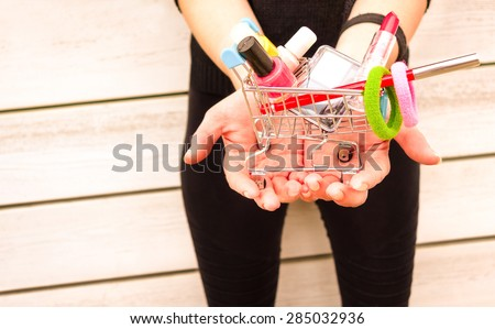 Young woman hands holding trolley with makeup objects and gadgets - Female vanity and shopping addiction - Girl with colorful beauty products on wooden background - Light pink vintage filter  - stock photo