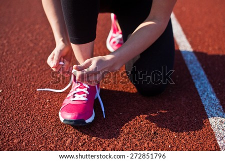 Young woman hands tie laces on her pink sport shoes on a stadium on a running path. White stripe near her. Close-up of tying shoes - stock photo