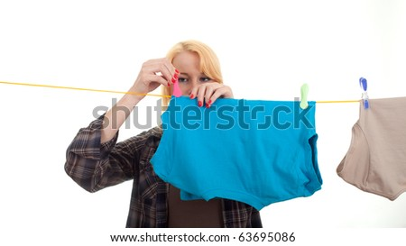 young woman hanging clothes on clothesline using clothespin - stock photo