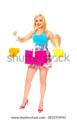 Young woman hanging laundry with huge clothespin - stock photo