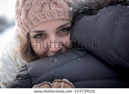 Young woman happiness. Close-up portrait of young woman, embracing boyfriend in winter park. - stock photo