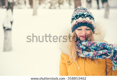 Young Woman happy smiling wearing hat and scarf walking outdoor winter snow Travel Fashion Lifestyle  - stock photo