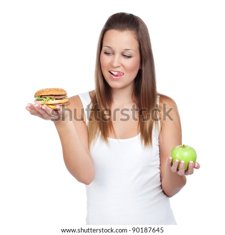 Young woman having a dilemma: greasy hamburger or an apple? Isolated on white