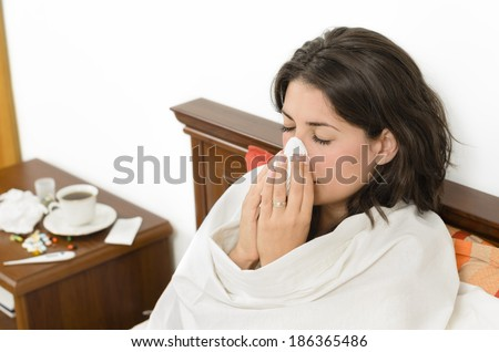 Young woman having a flu and sneezing