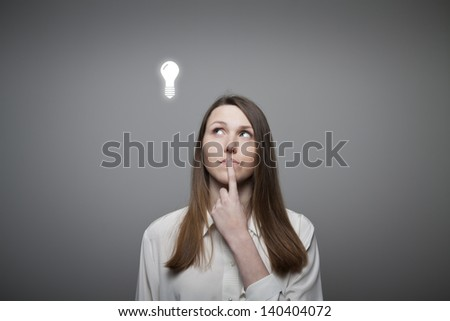 Young woman having an idea with light bulb over her head. - stock photo