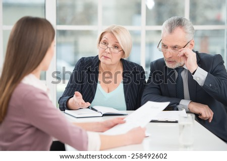 Young woman having an interview or business meeting with employers. Office interior with big window - stock photo