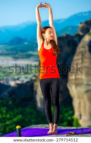 Young woman having exercise on the mat  in the mountains - stock photo