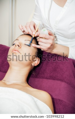 Young woman having eye makeup applied in a beauty salon - stock photo